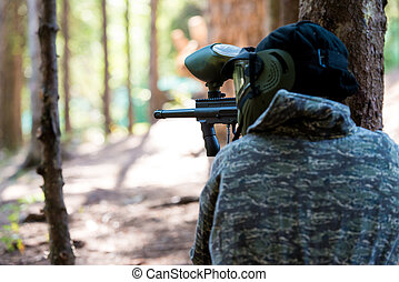 Paintball Players Hide Behind Tree
