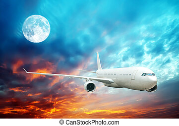 A plane flying high in the nighttime sky with an illuminated...