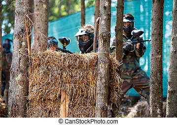 Paintball Players Hide Behind Tree - Paintball sport player...
