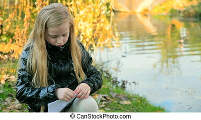 Child making a paper boat in the autumn park near the pond