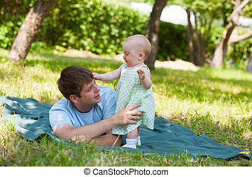 Father plays with the small daughter in the street