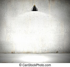 Stone blank wall illuminated with hanging above lamp. Place...