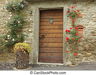 front door decorated with climbing roses in old tuscan...