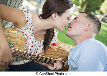 Mixed Race Couple with Guitar Kissing in the Park
