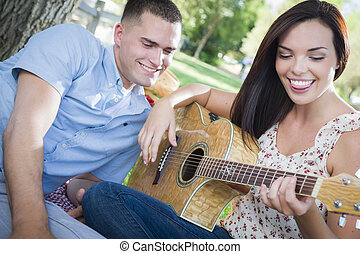 Mixed Race Couple at the Park Playing Guitar and Singing