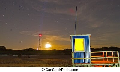 lifeguard hut on the beach at night , time-lapse