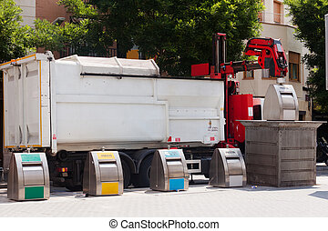 Garbage truck collects garbage dumpster in street
