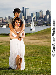 Vertical photo of young adult couple, facing forward, holding each with city of Seattle and harbor in Background