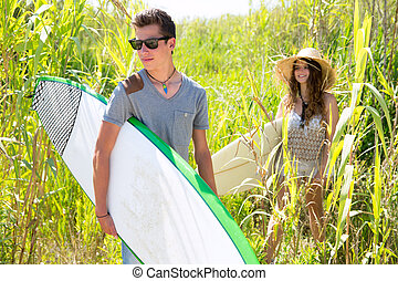 Surfer boy and girl walking in the green jungle with...