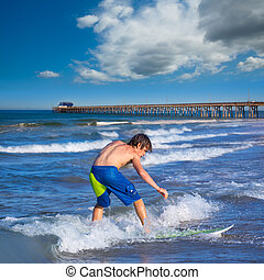 Boy surfer surfing waves on the Newport beach - Boy surfer...
