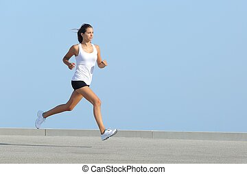 Beautiful sportswoman running with the sky in the background...