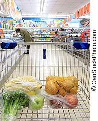 shopping cart with grocery at supermarket - view of a...