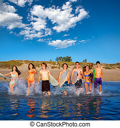 Teen surfers group running beach splashing - Teen surfers...