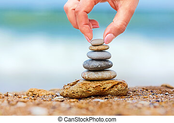 Hand placing the last pebble of a stacked tower on the sea...