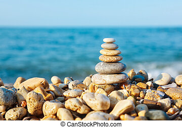 Stacked pebbles on the sea side - Differently sized and...