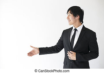 front view man extending hand - asian man in suit extending...