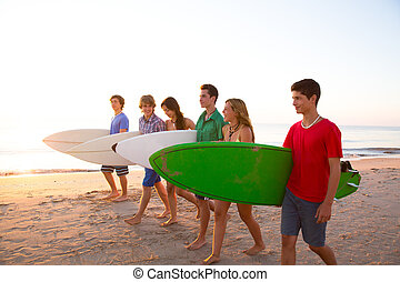 Surfer teen boys girls group walking on beach at sunshine...