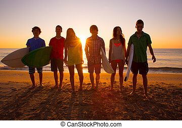 Surfers boys and girls group walking on beach - Surfers teen...