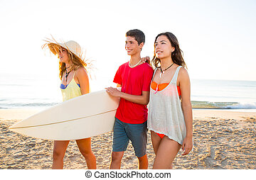 Surfer girls with teen boy walking on beach shore high key