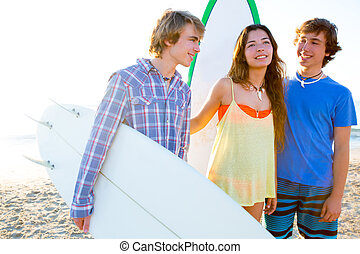 Teenager surfers group happy in beach shore high key