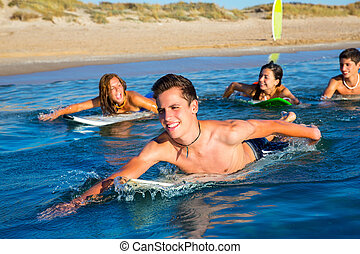 Teenager surfer boys and girls swimming ove surfboard -...