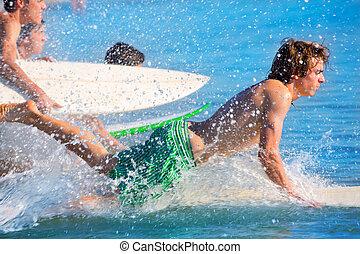 Boys surfers surfing running jumping on surfboards - Boys...