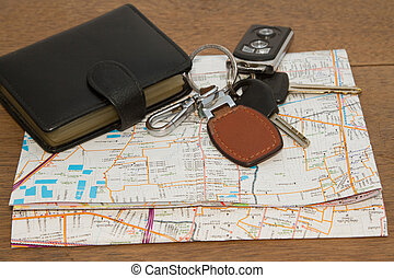 Wallet and car keys on the road map, concept travelling on...