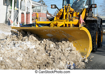 Snowplow in action - Snowplow clearing the street in a city