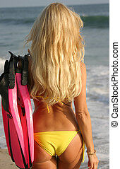 Woman walking towards the water with Fins - Woman with Fins...