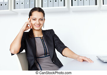 Young smiling business woman sitting at the desk - Portrait...