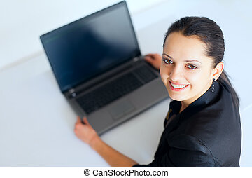 Young business woman working on a laptop - Portrait of...