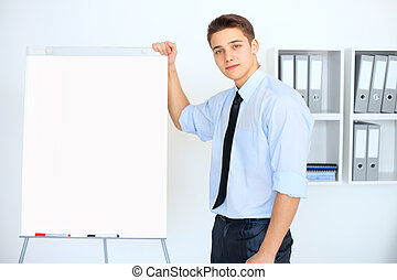 Young businessman with a flip chart during a presentation in...