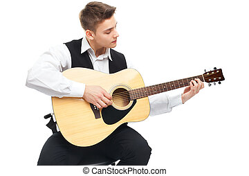 Young man playing on acoustic guitar sitting on a chair...