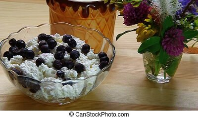 Blueberries stirred with a spoon with cottage cheese in a...