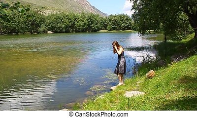Young beautiful girl in a dress dances on the shore of a...