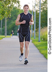 Young handsome sportsman running on the street