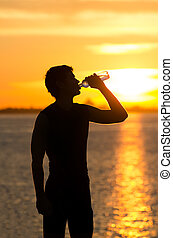 Man drinking bottle of water on the beach at sunrise