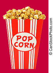 caramel popcorn in a decorative paper popcorn cup isolated...
