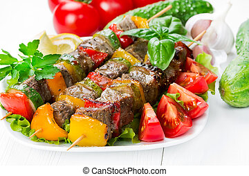 Grilled meat on skewers with vegetables on salad leaves