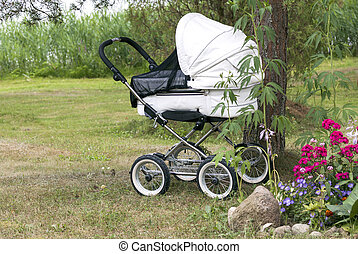 Modern white pram with supposedly sleeping baby under the...