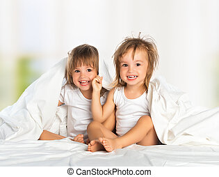 happy little girls twin sister in bed under the blanket...
