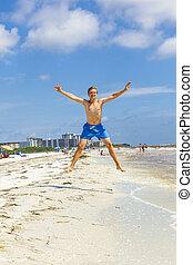 boy jumps in the air at the beach