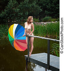 Naked girl with umbrella near small pond - Young naked girl...