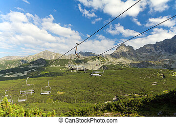 view on mountains in summer with ski lift on blue sky background