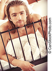 undress - Handsome nude man lying in a bed Isolated over...