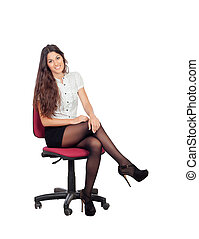 Pretty businesswoman in a stylish miniskirt sitting isolated...