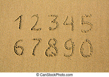 Numbers from one to ten, written on a sandy beach.