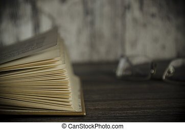 Vintage book, open, on old wooden table, with clipping path