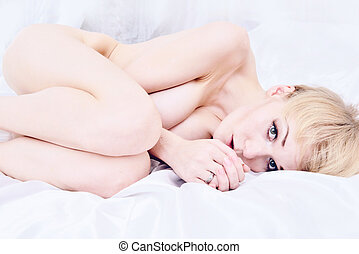 Beautiful naked blonde lying on the bed.