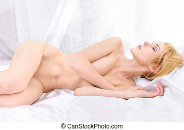 Beautiful naked woman lying on the bed,